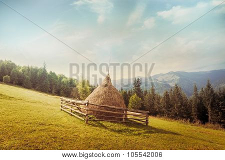 Hay Stack On Meadow At Suuny Morning