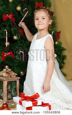 The little girl at a Christmas fur-tree with gifts