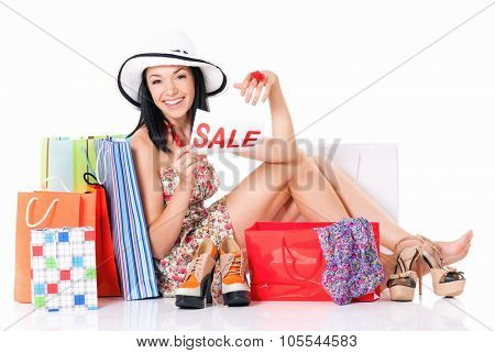 Shopaholic shopping woman with many shopping bags holding a signboard announcing a Sale, isolated on white background
