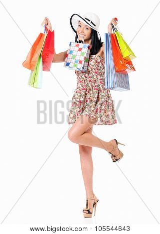 Young happy woman holding a shopping bags, isolated on white background