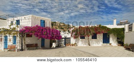 Beautiful white house with blue door surrounded by pink bougainvillea in Lefkes in Paros island in Greece