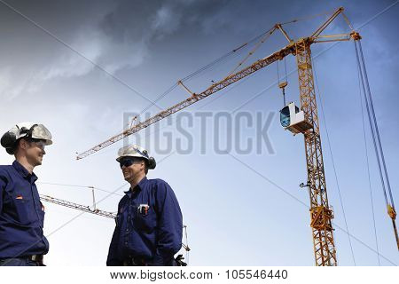 building workers with giant mobile construction cranes