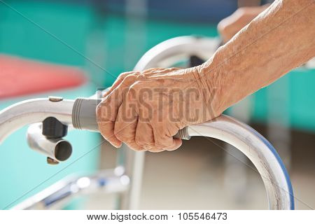 Old senior hands holding on to a walker for support