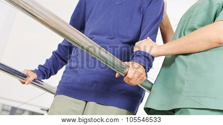 Hands of old woman on handles of a treadmill in physiotherapy