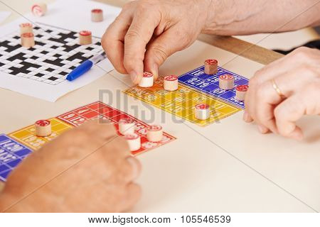 Hands of senior people playing Bingo together in a nursing home