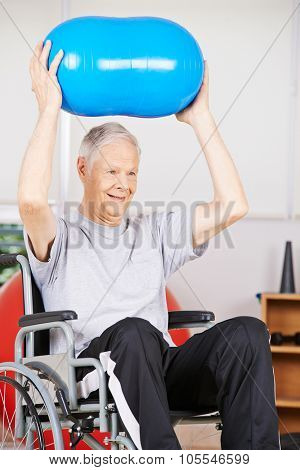 Old man in wheelchair in psychotherapy lifting a gym ball