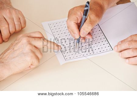 Hands of two senior people solving together a word search quiz