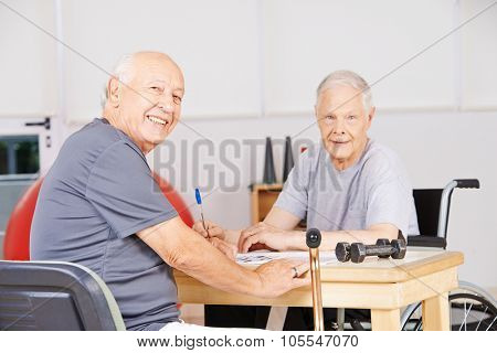 Two old men sitting in a nursing home and solving a crossword puzzle