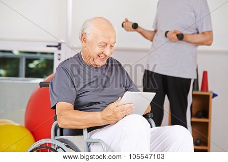 Disabled old man sitting in wheelchair with tablet PC in a nursing home
