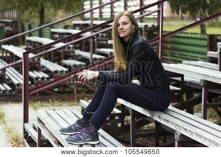 Young beautiful girl look and listening music on your mobile phone on the old stadiums bench