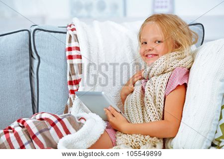 Little girl with sore throat holding tablet closeup