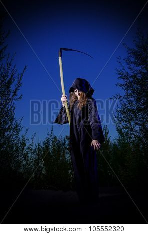Zombie girl with scythe in night forest