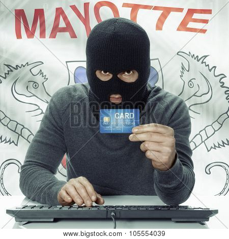 Dark-skinned Hacker With Flag On Background Holding Credit Card - Mayotte