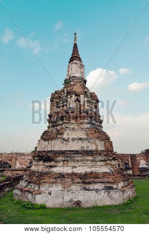 Old damaged buddha pagoda temple with cloudy white sky in Ayuthaya Thailand