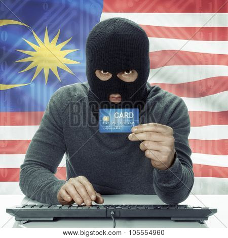 Dark-skinned Hacker With Flag On Background Holding Credit Card - Malaysia