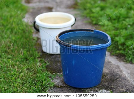 Two Buckets Standing On The Road In The Garden