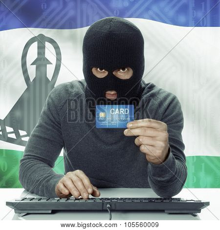 Dark-skinned Hacker With Flag On Background Holding Credit Card - Lesotho