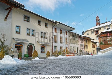View Of The Main Street In The Swiss Town Gruyeres Covered With Snow