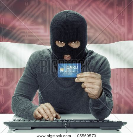 Dark-skinned Hacker With Flag On Background Holding Credit Card - Latvia