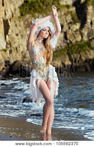 Girl Dressed Like A Mermaid Is Standing On The  Beach