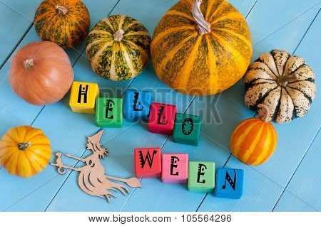 Word Helloween On child's toy cubes and pumpkins with witch silhouette on rural wooden background.