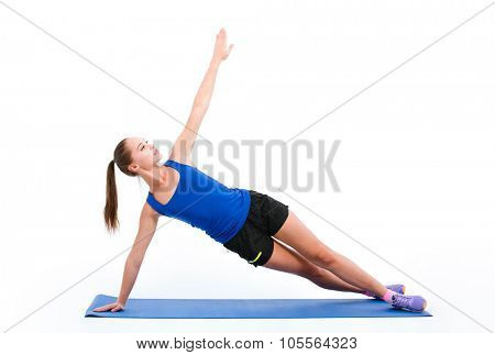 Young beautiful sportswoman in navy top and black shorts doing yoga