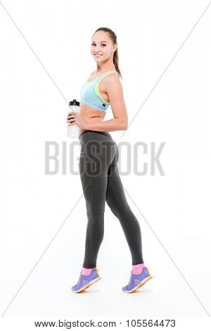 Full length portrait of a beautiful sports woman holding shaker and looking back at camera isolated on a white background