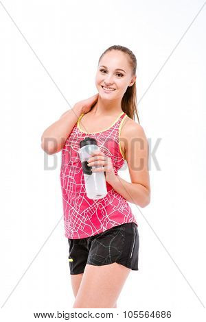 Young smiling beautiful sportswoman in pink top and black shorts with bottle of water