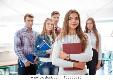Portrait of a young female student standing in classroom with classmates on background