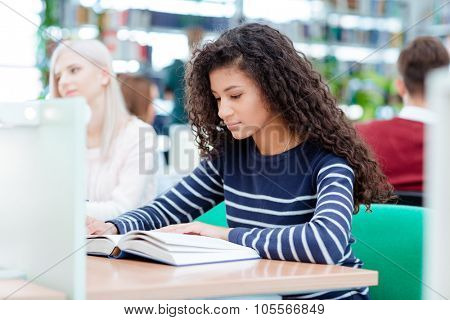 Young afro american woman reading book in classroom with classmates on background