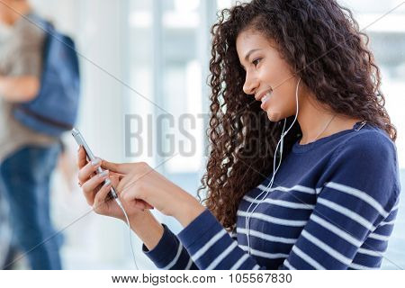 Happy afro american woman using smartphone with headphones in university hall