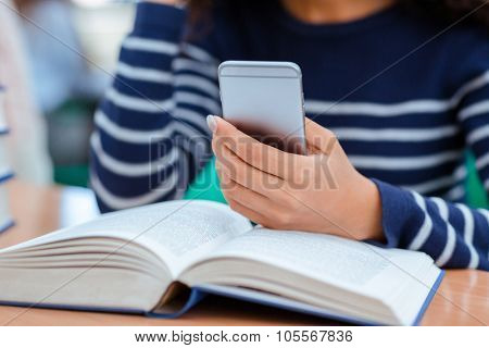 Woman stopped reading a book and took her cellphone in her hands