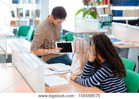 Asian man showing something on blank tablet computer screen to his classmates in university library