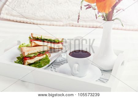 breakfast on wooden tray in bed sandwich and coffee