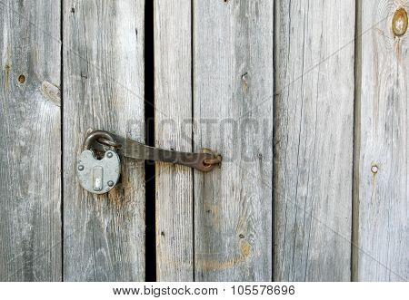 Old Metal Padlock Hanging On The Woden Door
