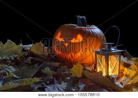 Spooky Jack O Lantern Among Dried Leaves On Black