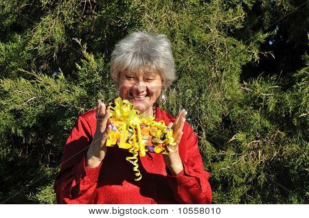 A happy, middle-aged woman holding a gift with both hands