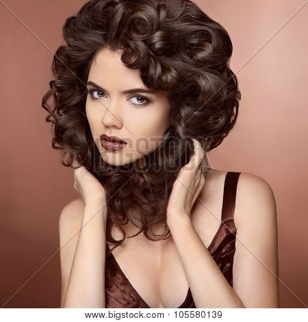 Beauty Model Girl With Healthy Brown Hair. Beautiful Brunette Woman Touching Her Curly Smooth Shiny