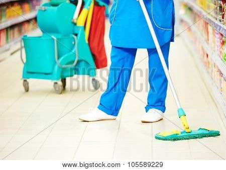 cleaning services. female cleaner in uniform  with mop the floor in supermarket shop store