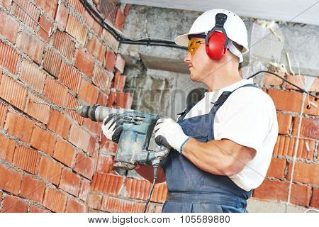 Builder worker with pneumatic hammer drill perforator equipment making hole in wall at construction site