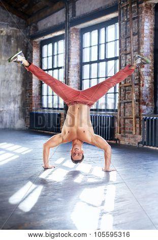 Young man break dancing in old sunny urban interior