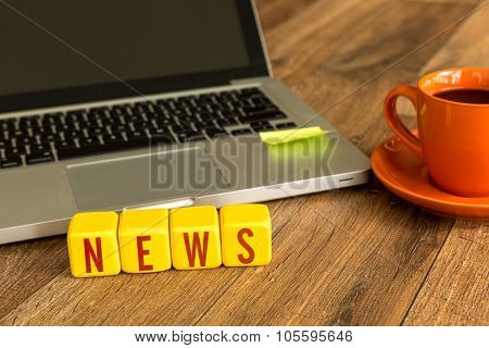 News written on a wooden cube in front of a laptop