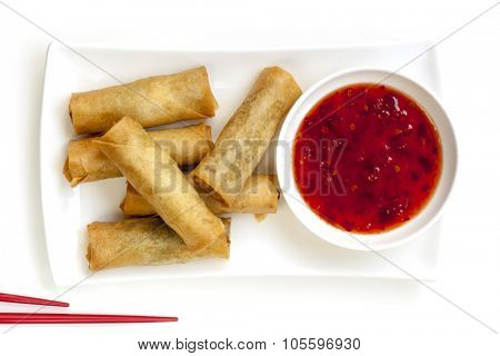 Spring rolls with chili sauce and chopsticks.  Overhead view.