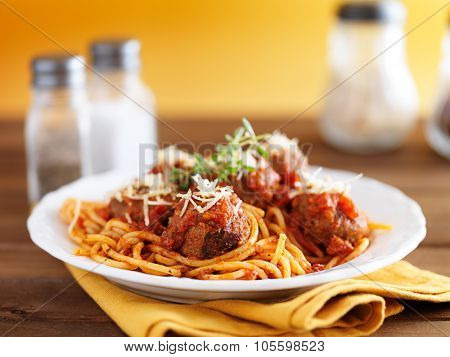 spaghetti and meatballs on rustic wooden table with yellow background