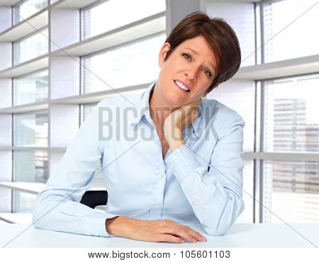 Tired business woman with headache migraine over office background.