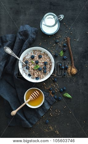Rustic healthy breakfast set. Cooked buckwheat groats with milk, blueberries and honey on dark grung