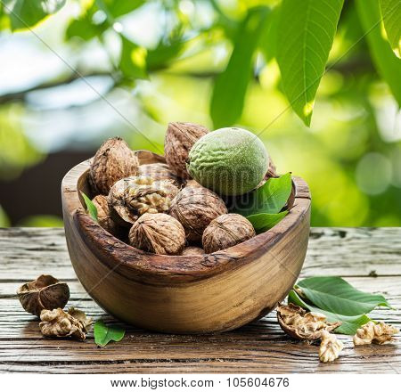 Walnuts in the wooden bowl on the table under the walnut-tree.