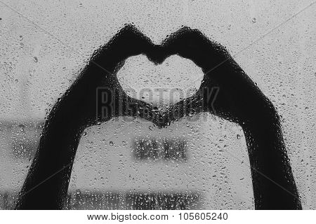 Blurred Background :hand Making The Sign Of Love With The Glass Background