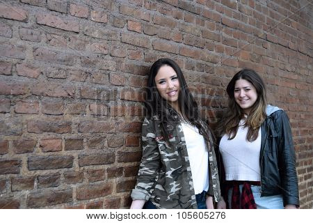 Two Hispanic Women Against A Brick Wall.