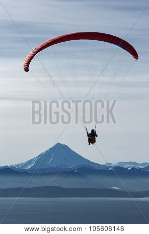 Paraglider Flying On Background Of Volcano And Sea